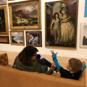 A mother and her son sit on a couch facing a grouping of paintings on the wall opposite.