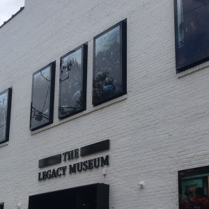"Image of the exterior of the museum with the words ""The Legacy Museum"" written on the front of a white painted brick building with sets of three dark windows across the front two story building."