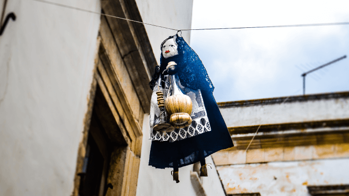 a witch doll hanging from a clothes-line holiday traditions
