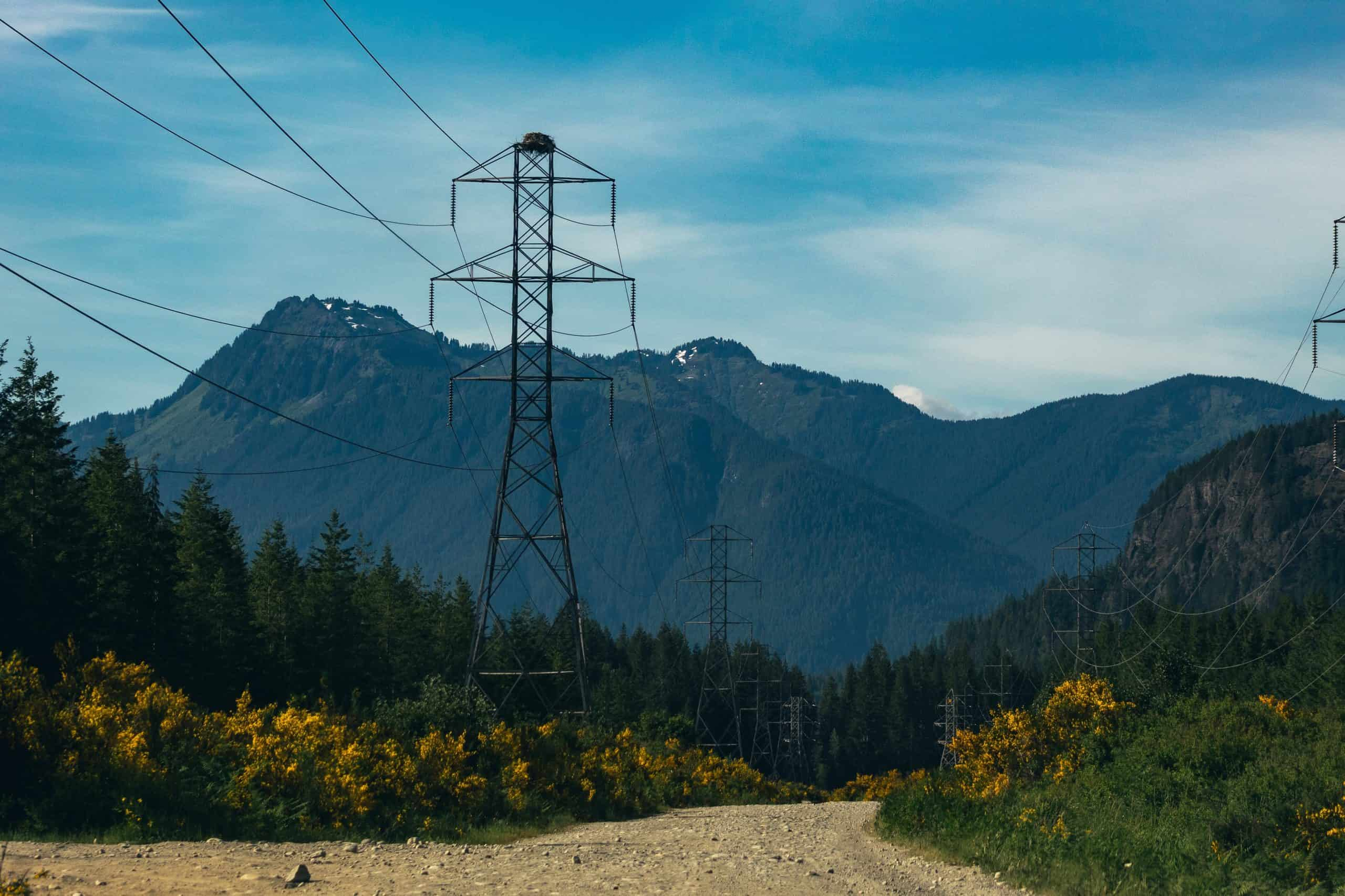 transmission lines in front of mountains