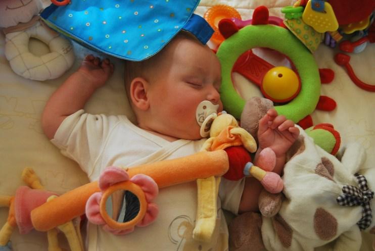 Baby mit Schnuller und Spielsachen