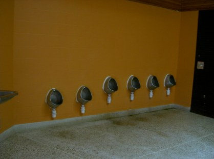 Urinals on an orange wall