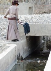 Cleaning Mops in Irrigation Canal