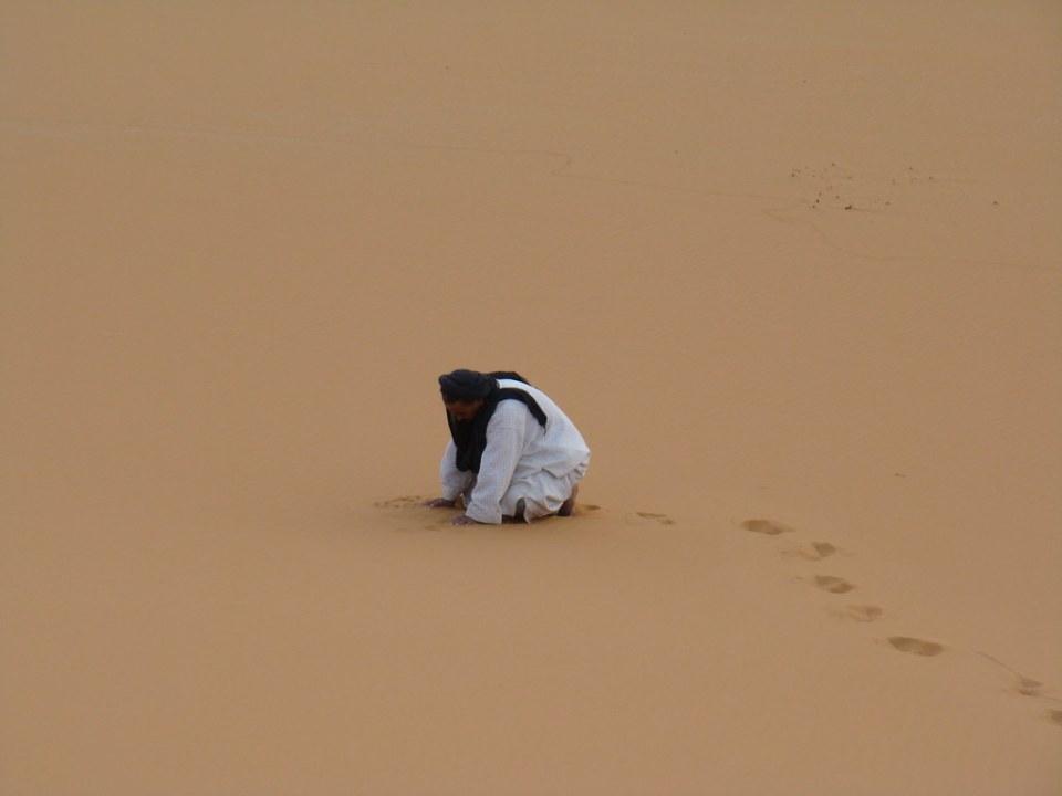 hombre musulman orando en la arena del desierto Dunas de Merzouga Erg Chebbi su gente Marruecos 024