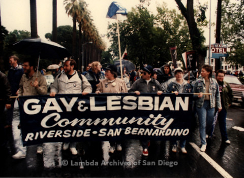 """P019.393m.r.t March on Sacramento 1988: People marching while holding banner that reads: """"GAY & LESBIAN COMMUNITY RIVERSIDE  SAN BERNARDINO"""""""