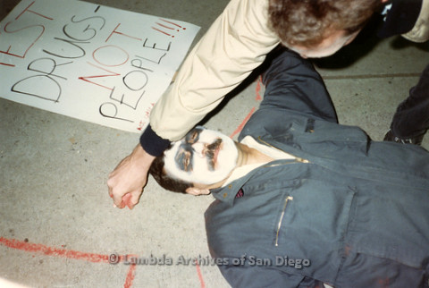 "P019.334m.r.t Los Angeles ""Die In"" 1988:  Man with skull face paint laying on ground with another man drawing chalk outline around him"