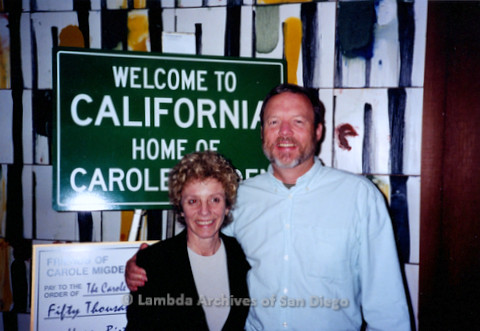 """P338.011m.r.t Charles McKain with Carole Midgen standing in front of a """"Welcome to California / Home of Carole Midgen"""" sign"""