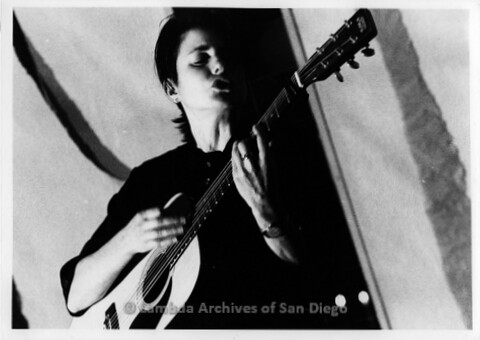 October 1993 - San Diego Native, Zanne in Germany: Lesbian Performer, Close-up of Zanne playing guitar.