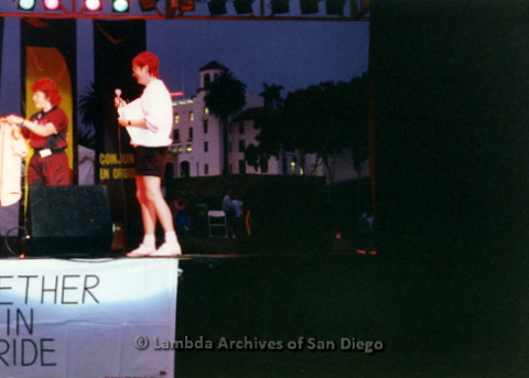 """P119.013m.r.t San Diego Pride: Two women on a stage over a """"Together in Pride"""" banner"""