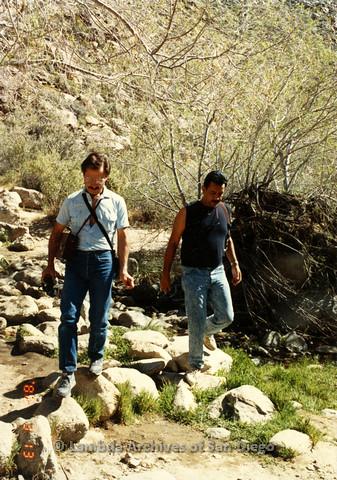 P099.097m.r.t Two men walking on rocks in front of a hill