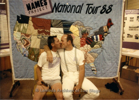 P019.190m.r.t AIDS Quilt at San Diego Golden Hall 1988: Albert Bell (left) and another man kissing in front of quilt