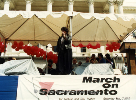 P019.173m.r.t March on Sacramento 1988 / Pre Parade gathering: Woman on stage speaking into microphone