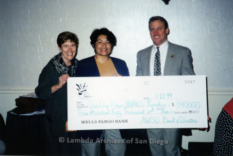 P240.052m.r.t AIDS Walk San Diego: Karen Marshall, unknown woman, and unknown man smiling at camera holding a check for $340,000 to the San Diego Region HIV/AIDS Providers