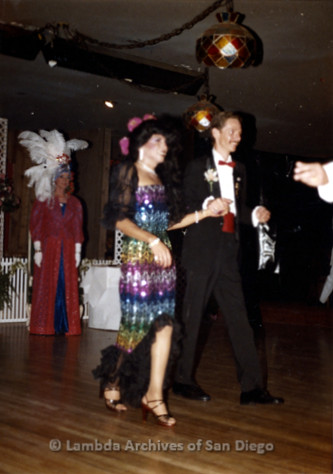 1983 - Imperial Court de San Diego Coronation Ball: HIM - Empress III Venus and HIM - Emperor II Glen McManus walking across the ballroom, during the Court Processional Introductions.