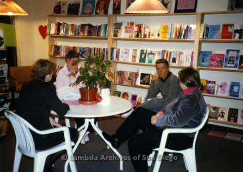 P169.068m.r.t Paradigm Women's Bookstore Grand Opening: Four women sitting around table at bookstore socializing