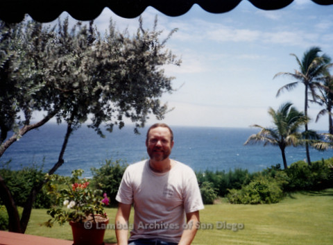 P338.069m.r.t Charles McKain sitting on bench in Maui, ocean and palm trees in background