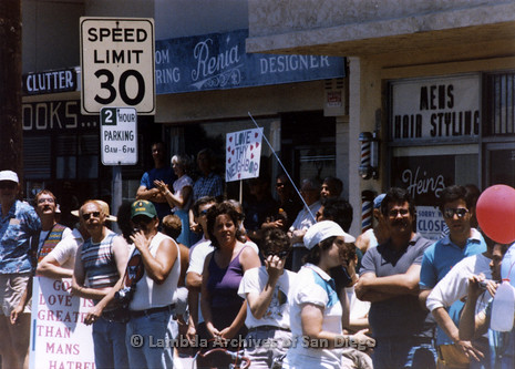 """San Diego Lambda Pride Parade: Crowd holding Pro-LGBT signs across the street from Fundamentalist Christian Protesters. Two Pro-LGBT signs visible, """"Love Thy Neighbor"""" and """"God's Love is Greater Than Man's Hatred"""" sign in background."""