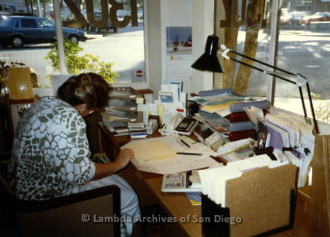 P168.047m.r.t Paradigm Women's Bookstore Kettner Location: Woman working at desk near windows