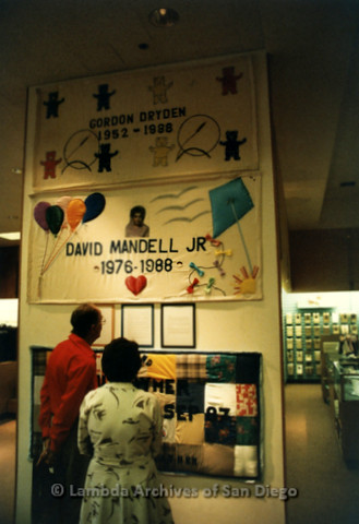 P019.082m.r.t AIDS Quilt at San Diego Golden Hall 1988: Two people looking at quilts dedicated (top to bottom) to Gordon Dryden, David Mandell Jr, and Bill Rymer