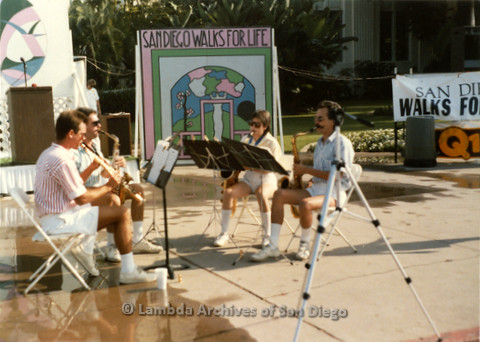"""P197.001m.r.t San Diego Walks for Life 1988: Four people playing instruments in front of a sign that reads: """"San Diego Walks For Life"""""""