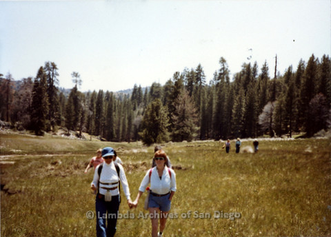 P008.033m.r.t Harvey Moore Trail 1983: Gretchen Alspach and Diane F. Germain holding hands in a field