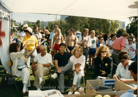 P012.017m.r.t San Diego Walks for Life 1986: Michael Tuck (seated center), Eileen Brennan (black coat) and others sitting in a First Aid Tent