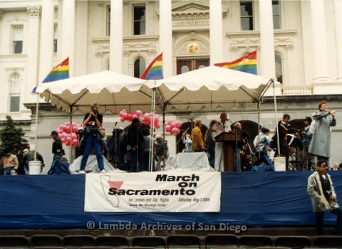 P019.162m.r.t March on Sacramento 1988 / Pre Parade gathering: Man speaking at podium on stage while a woman takes photos of the audience