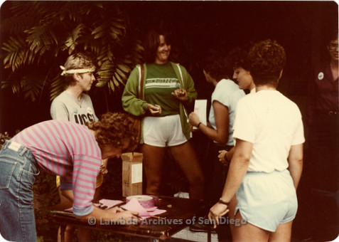 Blood Sisters blood drive, 1983: Carol Adsit speaking with guests at check-in table outside Blood Bank