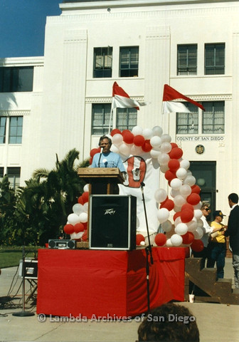 P012.008m.r.t San Diego Walks for Life 1986: Man in blue shirt speaking at podium