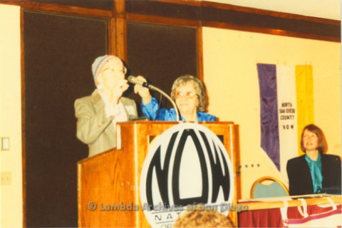 National Organization for Women, Susan B. Anthony Awards 1992: Ann Ramsey (left) at podium on stage, Gloria Johnson President of San Diego NOW (center) adjusting the microphone.