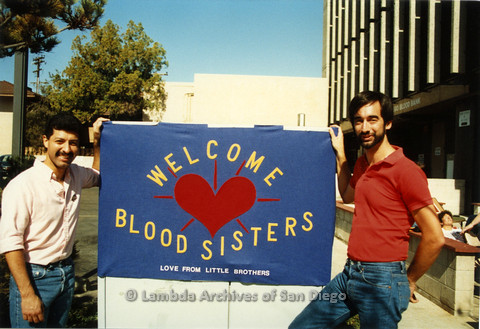 "P019.077m.r.t AIDS Quilt at San Diego Golden Hall 1988: Henry Ramirez (left) and another man holding ""Welcome Blood Sisters"" sign in front of Blood Bank"