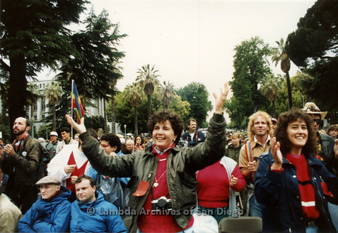 P019.113m.r.t March on Sacramento 1988 / Pre Parade gathering: Two women standing with both hands up in front of a crowd