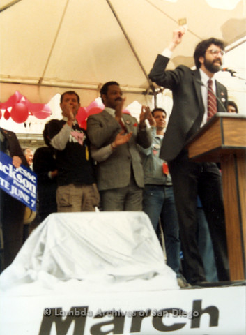 P019.132m.r.t March on Sacramento 1988 / Pre Parade gathering: David Scondras speaking at podium on stage with Jesse Jackson standing behind him