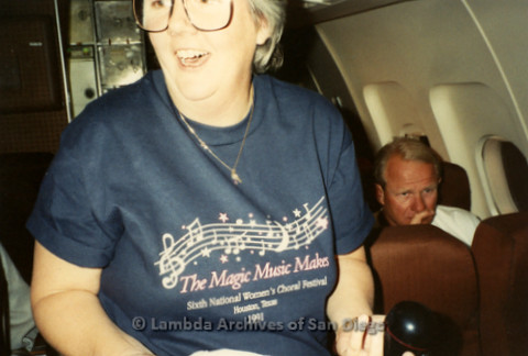 """""""The Magic Music Makes"""" San Diego Women's Chorus (SDWC) first choral festival with Sister Singers 1991: SDWC member on the plane wearing 'The Magic Music Makes' shirt from the Choral Festival. Date: November 1991"""