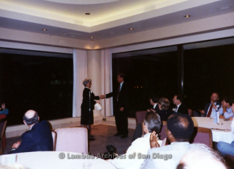 P341.038m.r.t Man shaking hands with woman speaker in front of audience