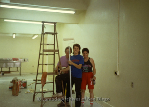 P169.019m.r.t Paradigm Women's Bookstore - Moving in: Three women posing in unfinished room with ladder and paint roller