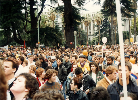 P019.155m.r.t March on Sacramento 1988 / Pre Parade gathering: Shot of audience, including a man holding up a large cross