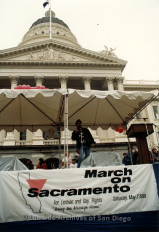 P019.177m.r.t March on Sacramento 1988 / Pre Parade gathering: Man speaking on stage in front of City Hall