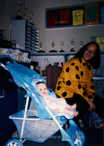 P240.066m.r.t The Center, Normal Street: Man in yellow and black shirt in Center office with baby in stroller