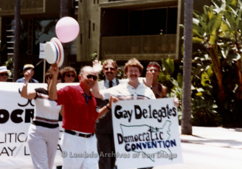 "P338.063m.r.t Herb King, Rob Sandler, Doug Scott and unidentified men walking in a San Diego Pride Parade holding a ""Gay Delegates Democratic Convention"" sign"