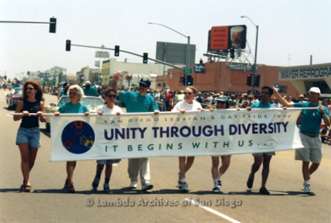 San Diego LGBTQ Pride Parade, July 1998: Judi Schaim (2nd left), Joe Mayer (4th left), Sheila Clark (rainbow hat), Judy Reif (3rd right) with other LGBT Pride Board members carrying the 1998 theme banner 'Unity Through Diversity, It Begins With Us...'