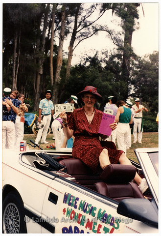 P201.039m.r.t San Diego Pride Parade 1991: Karen Merry sitting in convertible car representing her bookstore, Paradigm Women's Bookstore