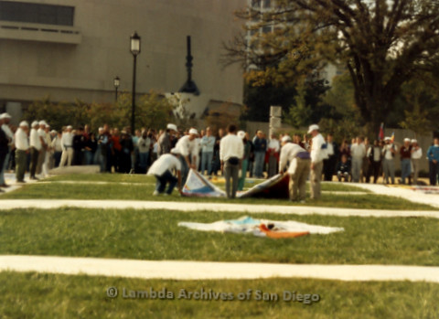 P019.295m.r.t AIDS Memorial Quilt 1987: Group of people positioning AIDS Memorial Quilt on large lawn