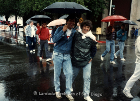P019.395m.r.t March on Sacramento 1988: Jeri Dilno marching on street, sharing a man's umbrella