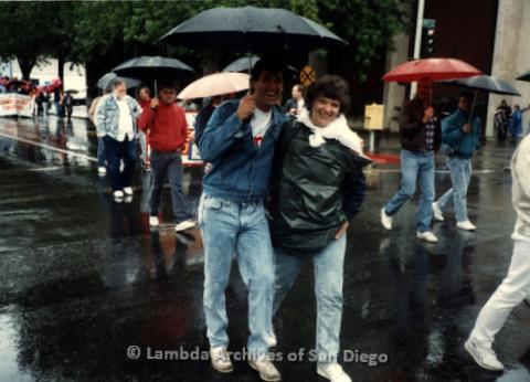 P019.395m.r.t March on Sacramento 1988: Jeri Dilno marching on street, sharing a man's umbrella