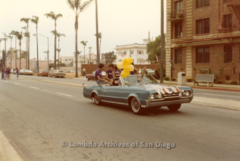 1982 - San Diego Pride Parade, 'W.C.P.C.' (West Coast Production Company) lead car drives up 6th. avenue on the Pride parade route.