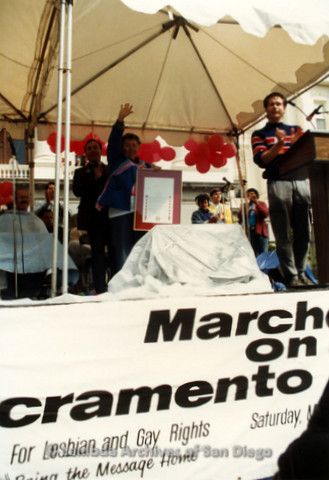 P019.165m.r.t March on Sacramento 1988 / Pre Parade gathering: People on stage woman is holding a framed later holding her hand in air.