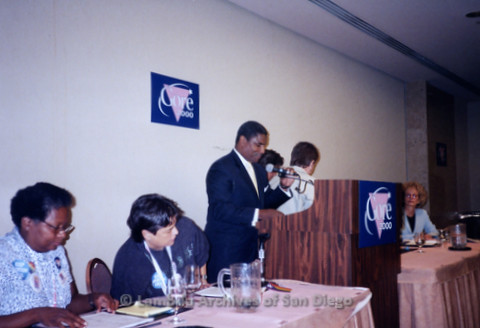 P338.044m.r.t 2000 Democratic National Convention Los Angeles: Man speaking at podium in front of Gore 2000 sign at the Gay Caucus meeting