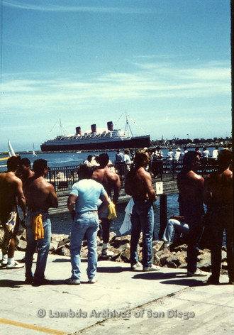 P243.033m.r.t Shirtless men standing at Long Beach Bay looking at the Queen Mary during Long Beach Gay Pride Festival 1989.