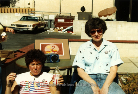 P019.079m.r.t AIDS Quilt at San Diego Golden Hall 1988: Jeri Dilno and another woman sitting in a parking lot